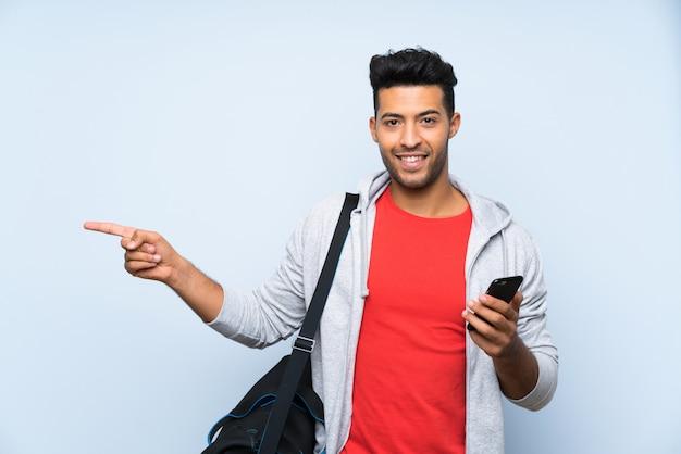 Homme de sport sur mur bleu isolé surpris et pointant le doigt sur le côté