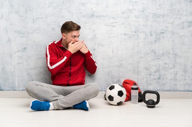 Homme de sport rousse couvrant la bouche et regardant sur le côté