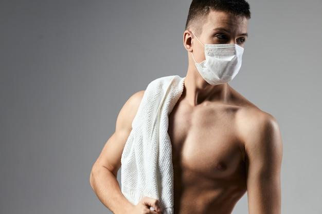 Homme de sport avec une serviette sur les épaules masque médical torse gonflé isolé