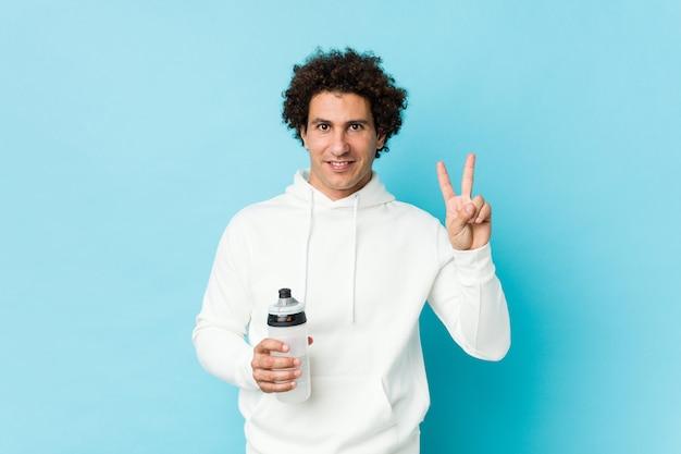 Homme de sport tenant une bouteille d'eau montrant le numéro deux avec les doigts.