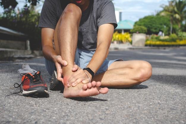 Homme de sport tenant la cheville dans la douleur due à une entorse à la cheville. blessure due au concept d'entraînement