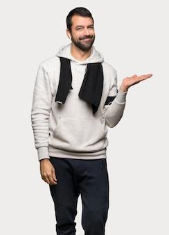 Homme de sport tenant une surface imaginaire sur la paume pour insérer une annonce sur un fond gris isolé