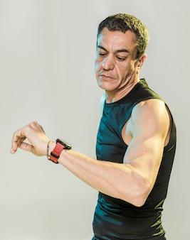 Homme sportif à angle élevé vérifiant la montre