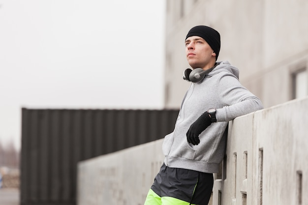 Homme sportif appuyé contre le mur