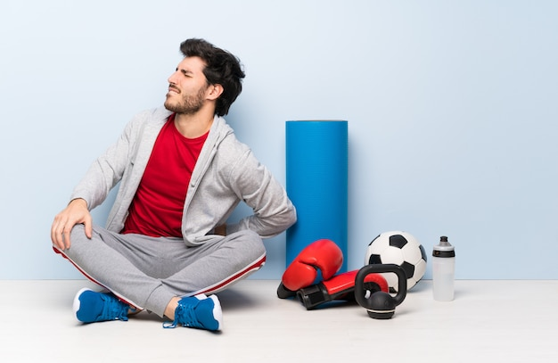 Homme sportif assis sur le sol, souffrant de maux de dos pour avoir fait un effort