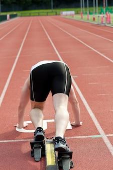Homme sportif attendant dans le bloc de départ