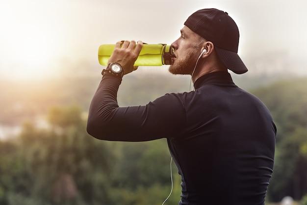 Un Homme Sportif Barbu En Gros Plan Se Repose Et Boit De L'eau Après La Séance D'entraînement. Photo Premium