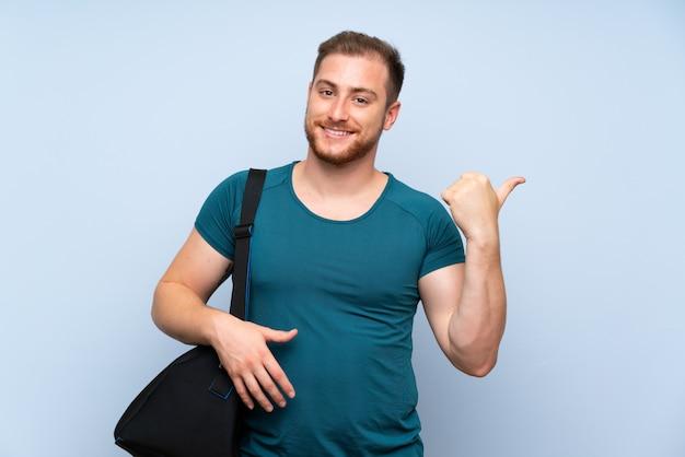Homme sportif blond sur un mur bleu pointant sur le côté pour présenter un produit