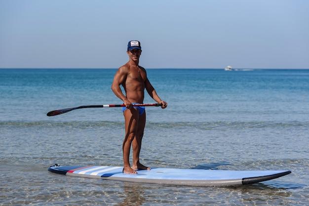 Homme sportif bronzé coiffé d'une casquette, debout sur sa planche de surf, tenant l'aviron entre les mains et regardant dans la mer.