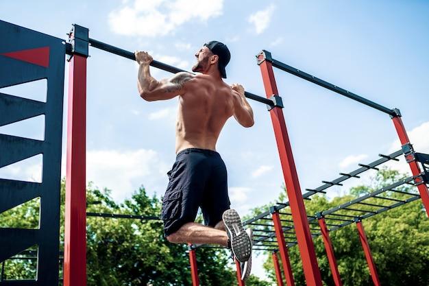 Homme sportif brutal faisant des exercices de traction sur une barre transversale.