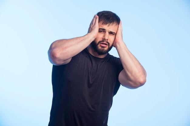Homme sportif en chemise noire couvrant sa tête.