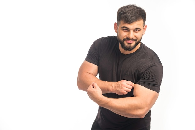 Homme sportif en chemise noire montrant ses biceps.