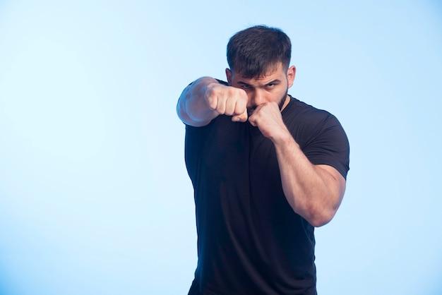 Homme sportif en chemise noire montrant des tours de boxe