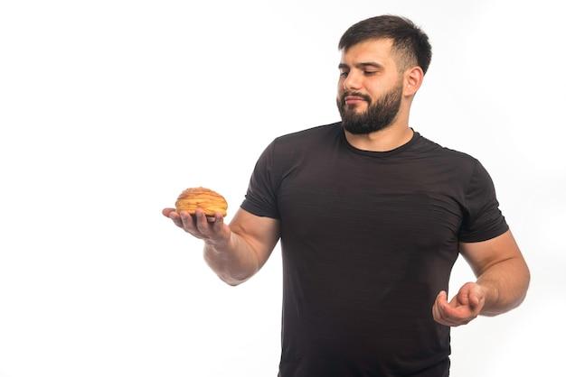 Homme sportif en chemise noire tenant un beignet.
