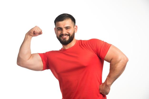 Homme sportif en chemise rouge démontrant ses muscles du bras et souriant.