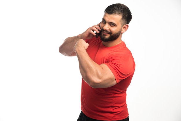 Homme sportif en chemise rouge parlant au téléphone et démontrant ses muscles des bras.
