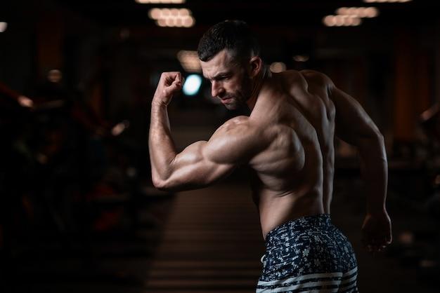 Homme sportif avec un corps musclé pose dans la salle de gym, exhibant ses biceps. le concept d'un mode de vie sain