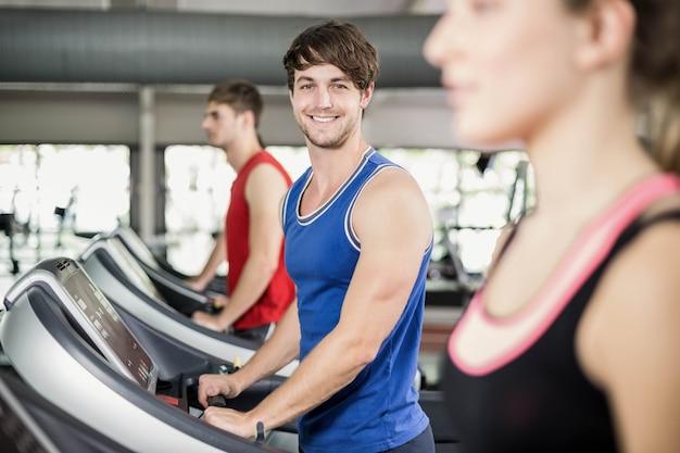 Homme sportif en cours d'exécution sur tapis roulant à la gym