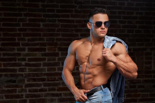 Homme sportif élégant en vêtements en denim.