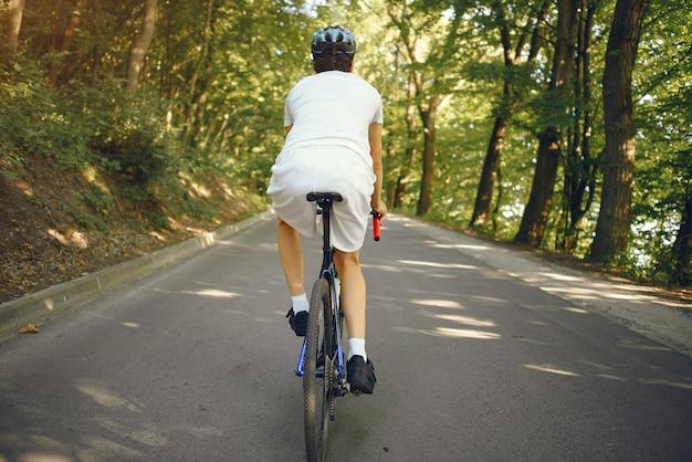 Homme sportif, faire du vélo dans la forêt d'été