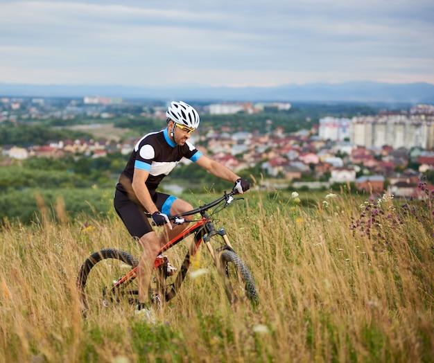 Homme sportif, faire du vélo sur le sentier dans l'herbe