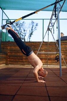 Homme sportif, faire de l'exercice avec des cordes sur un terrain de sport à l'extérieur