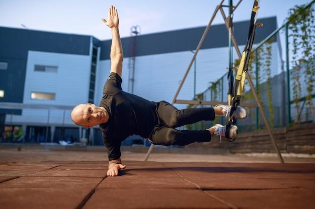 Homme sportif faisant des exercices d'équilibre avec des cordes sur un terrain de sport à l'extérieur