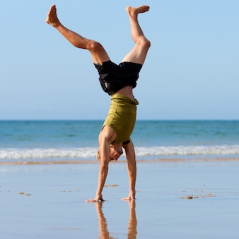 Homme sportif faisant de la gymnastique sur la plage