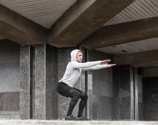 Homme sportif faisant des squats à l'extérieur