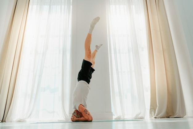 L'homme sportif fait du yoga à la maison