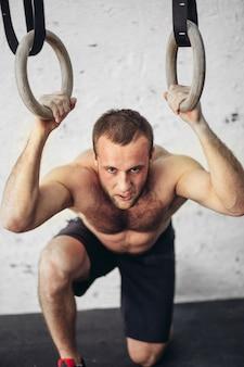 Homme sportif fatigué après l'entraînement sur les anneaux dans un club de gym