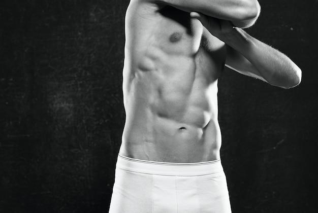Homme sportif avec un fond sombre du corps gonflé