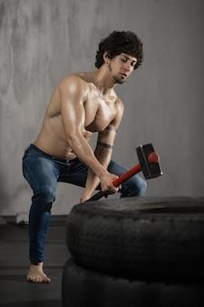 Homme sportif frappe pneu - entraînement au gymnase avec marteau