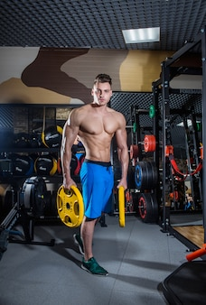 Homme sportif avec de gros muscles et un dos large s'entraîne dans le gymnase, fitness