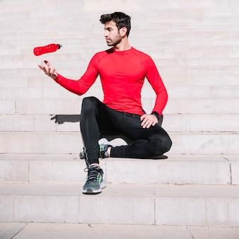 Homme sportif lancer une bouteille