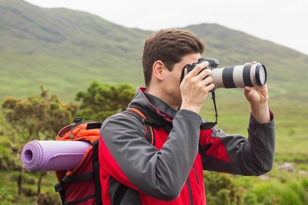 Homme sportif lors d'une randonnée en prenant une photo