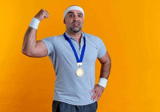 Homme sportif mature en bandeau avec médaille d'or autour de son cou levant le poing à la confiance debout sur le mur orange