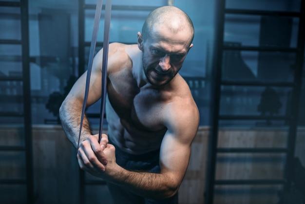 Homme sportif musclé avec de forts exercices de biceps avec bande élastique dans la salle de gym.