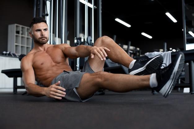 Homme sportif s'étirant et s'échauffant en faisant des exercices spéciaux pour les muscles avant de travailler son corps.
