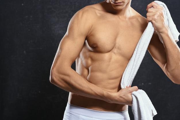 Un homme sportif en short blanc a gonflé une bouteille d'eau corporelle en bonne forme physique
