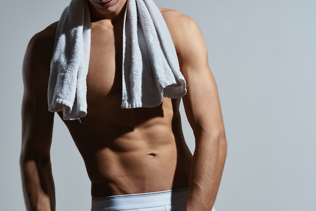 Homme sportif en short blanc posant une vue recadrée d'abs gonflés