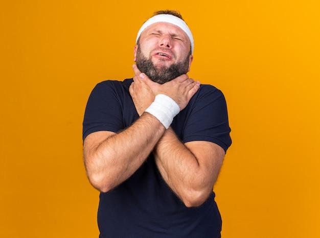 Homme sportif slave adulte douloureux portant un bandeau et des bracelets s'étouffant avec les mains isolées sur un mur orange avec espace de copie