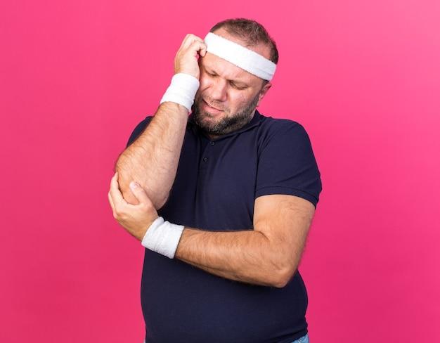 Homme sportif slave adultes endoloris portant un bandeau et des bracelets tenant son bras isolé sur un mur rose avec copie espace