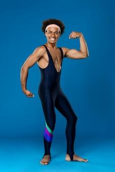 Homme sportif souriant, posant, montrant les muscles
