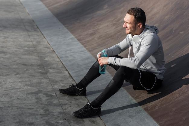 Homme sportif souriant tenant une bouteille d'eau et regardant au loin