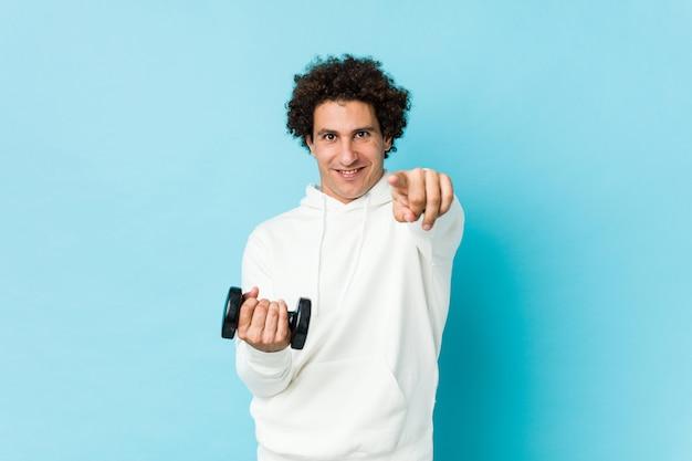 Homme sportif tenant un sourire joyeux dumbbel pointant vers l'avant.