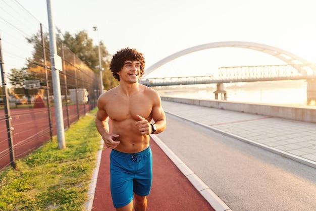 Homme sportif torse nu souriant courir sur la piste de course près de la rivière le matin