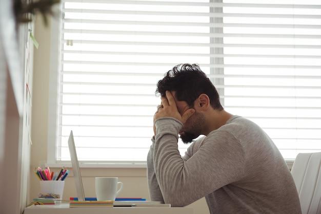 Homme stressé assis avec les mains sur la tête