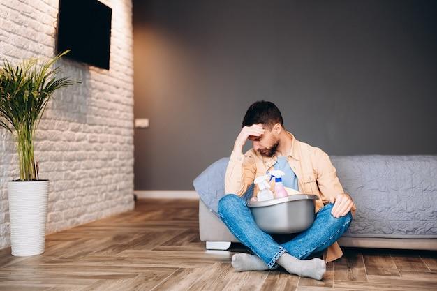 Homme stressé ayant l'air déçu avant le ménage, assis sur le sol avec des produits de nettoyage