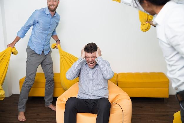 Homme stressé criant à des amis qui font du bruit